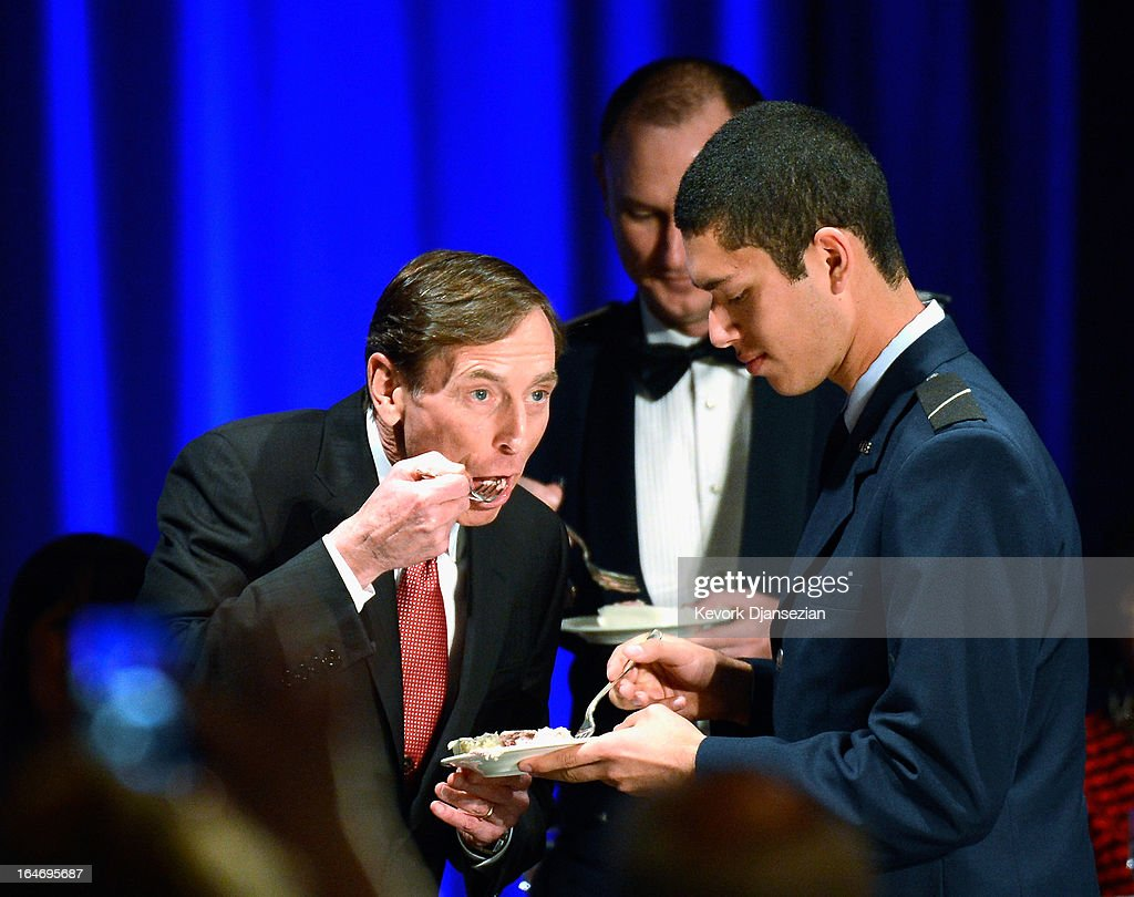 Former CIA director and retired four-star general General David Petraeus (C) shares a portion of a cake with armed sevices ROTC Hector Sandoval befotre making his first public speech since resigning as CIA director at University of Southern California dinner for students Veterans and ROTC students on March 26, 2013 in Los Angeles, California. Petraeus is expected to apologize in his speech for the extramarital affair that ended his extraordinary career.