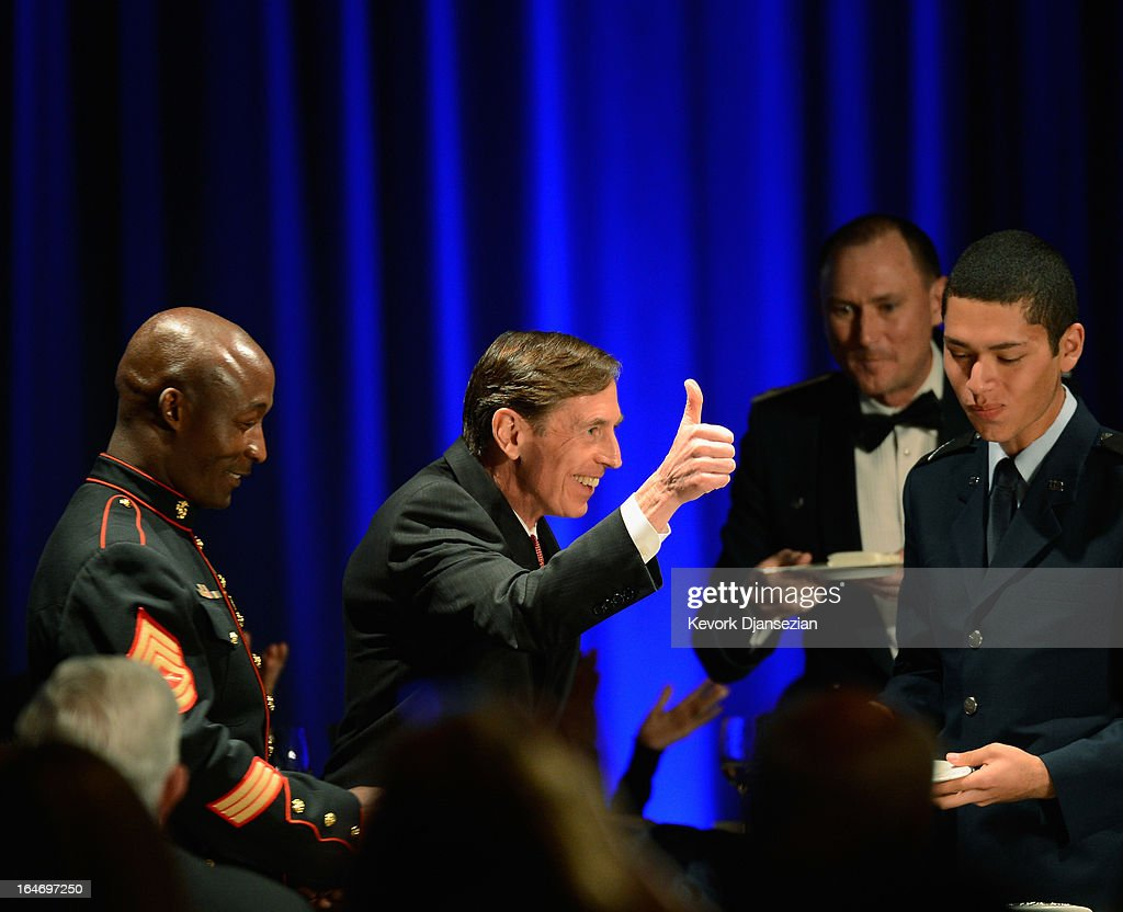Former CIA director and retired four-star general General David Petraeus (C) gives a thumbs up after sharing a portion of a cake with armed sevices ROTC Hector Sandoval (R) before making his first public speech since resigning as CIA director at University of Southern California dinner for students Veterans and ROTC students on March 26, 2013 in Los Angeles, California. Petraeus is expected to apologize in his speech for the extramarital affair that ended his career.