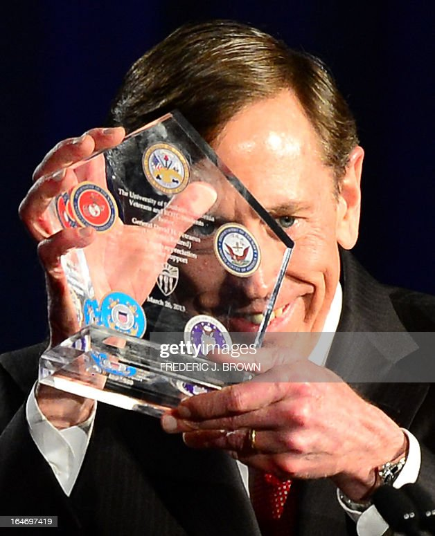 Former CIA director David Petraeus displays a token of appreciation presented to him following his address at a University of Southern California event honoring the military on March 26, 2013 in Los Angeles, California. In the first public appearance since stepping down last November as head of the CIA after admitting to an affair, Petraeus said he regretted and apologized for the circumstances that led to his resignation. AFP PHOTO / Frederic J. BROWN