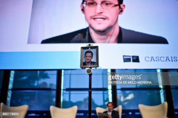 US former CIA employee and whistleblower Edward Snowden delivers a speech by video conference during the debate at the 'Estoril Conferences Global...