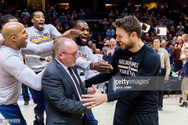 Former Cleveland Cavalier Matthew Dellavedova of the Milwaukee Bucks is mobbed by his former teammates as Cavs general manager David Griffin presents...