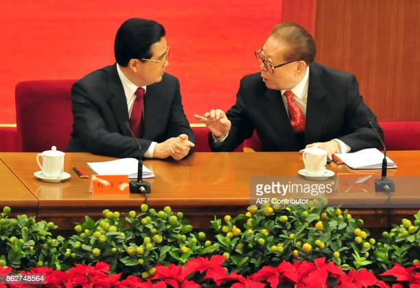 Former Communist Party leader Jiang Zemin gestures while talking to Chinese President Hu Jintao as top Communist Party leaders attend an event...