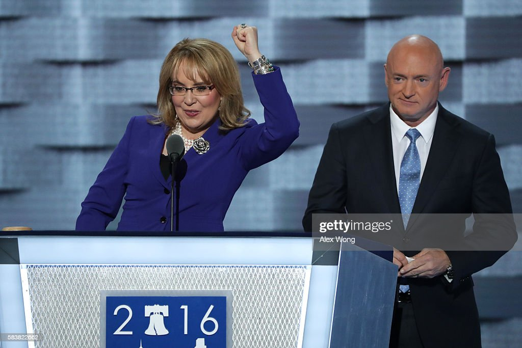 Former Congresswoman Gabby Giffords gestures to the crowd as her husband retired NASA Astronaut and Navy Captain Mark Kelly looks on after delivering...