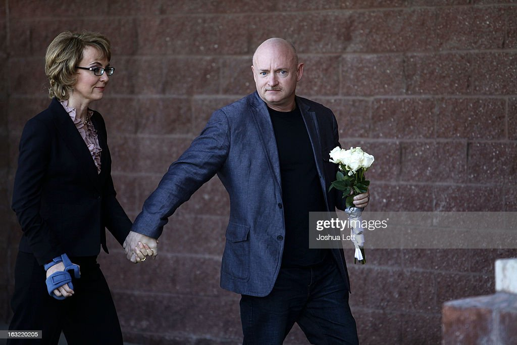 Former Congresswoman Gabby Giffords holds the hand of her husband Mark Kelly as they attend a news conference asking Congress and the Senate to provide stricter gun control in the United States on March 6, 2013 in Tucson, Arizona. Giffords and Kelly were joined by survivors of the Tucson shooting as they spoke outside the Safeway grocery store where the shooting happened two years ago where six people were killed.