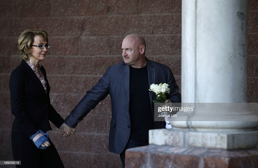 Former Congresswoman Gabby Giffords holds the hand of her husband <a gi-track='captionPersonalityLinkClicked' href=/galleries/search?phrase=Mark+Kelly+-+Astronaut+and+Gun+Control+Advocate&family=editorial&specificpeople=566699 ng-click='$event.stopPropagation()'>Mark Kelly</a> as they attend a news conference asking Congress and the Senate to provide stricter gun control in the United States on March 6, 2013 in Tucson, Arizona. Giffords and Kelly were joined by survivors of the Tucson shooting as they spoke outside the Safeway grocery store where the shooting happened two years ago where six people were killed.