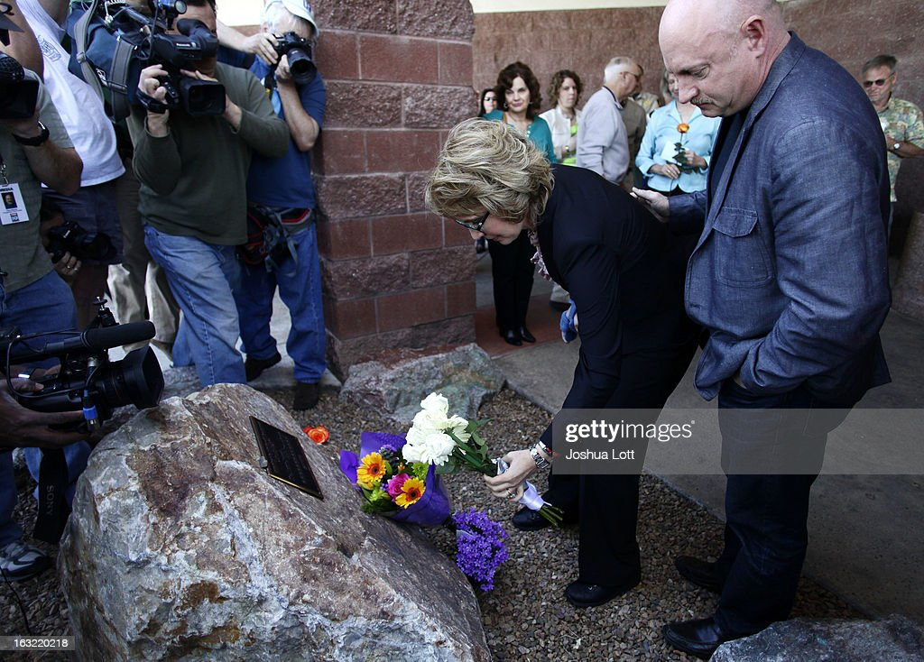 Former Congresswoman Gabby Giffords places flowers at a memorial with her husband <a gi-track='captionPersonalityLinkClicked' href=/galleries/search?phrase=Mark+Kelly+-+Astronaut+and+Gun+Control+Advocate&family=editorial&specificpeople=566699 ng-click='$event.stopPropagation()'>Mark Kelly</a> before they attend a news conference asking Congress and the Senate to provide stricter gun control in the United States on March 6, 2013 in Tucson, Arizona. Giffords and Kelly were joined by survivors of the Tucson shooting as they spoke outside the Safeway grocery store where the shooting happened two years ago where six people were killed.