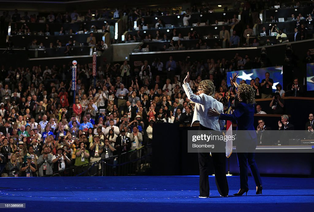 Former congresswoman Gabrielle Giffords, left, and Representative Debbie Wasserman Schultz, a Democrat from Florida, wave before reciting the Pledge of Allegiance during day three of the Democratic National Convention (DNC) in Charlotte, North Carolina, U.S., on Thursday, Sept. 6, 2012. President Barack Obama's prime-time nomination acceptance speech tonight at the DNC will be aimed at convincing voters that a slow economic recovery will accelerate if they give him a second term. Photographer: Andrew Harrer/Bloomberg via Getty Images