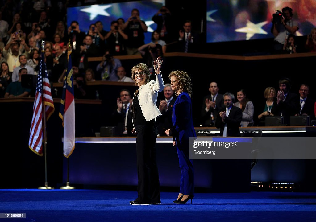 Former congresswoman Gabrielle Giffords, left, waves with Representative Debbie Wasserman Schultz, a Democrat from Florida, before reciting the Pledge of Allegiance during day three of the Democratic National Convention (DNC) in Charlotte, North Carolina, U.S., on Thursday, Sept. 6, 2012. President Barack Obama's prime-time nomination acceptance speech tonight at the DNC will be aimed at convincing voters that a slow economic recovery will accelerate if they give him a second term. Photographer: Andrew Harrer/Bloomberg via Getty Images