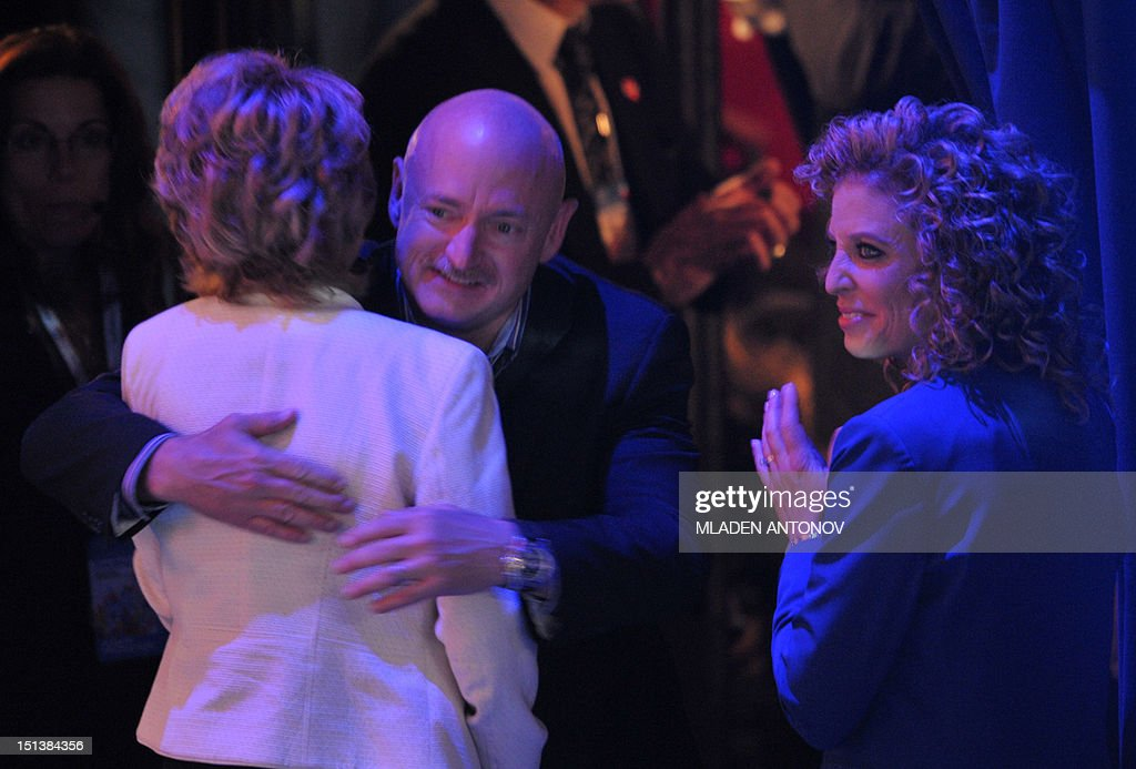 Former congresswoman Gabrielle Giffords receives a hug from husband astronaut Mark Kelly as Chair of the Democratic National Committee Debbie Wasserman Schultz (L) claps after Giffords delivered the Pledge of Allegiance at the Time Warner Cable Arena in Charlotte, North Carolina, on September 6, 2012 on the final day of the Democratic National Convention (DNC). US President Barack Obama is expected to accept the nomination from the DNC to run for a second term as president. AFP PHOTO Mladen ANTONOV