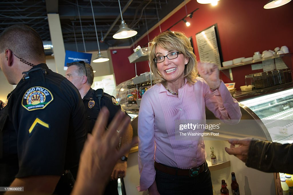 Former Congresswoman Gabrielle Giffords smiles and waves to a crushed room of supporters at a local coffeeshop, Atomic Coffee, during the Americans for Responsible Solutions tour in Fargo, North Dakota, on Wednesday, July 3, 2013.