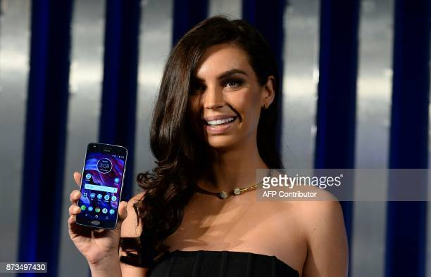 Former contestant of 'MasterChef Australia' Sarah Todd holds the newly launched Lenovoowned Motorola Moto X4 smartphone during a promotional event in...