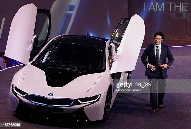 Former cricket player Sachin Tendulkar poses next to the BMW i8 a hybrid sports car during its launch on February 18 2015 in Mumbai India At Rs 229...
