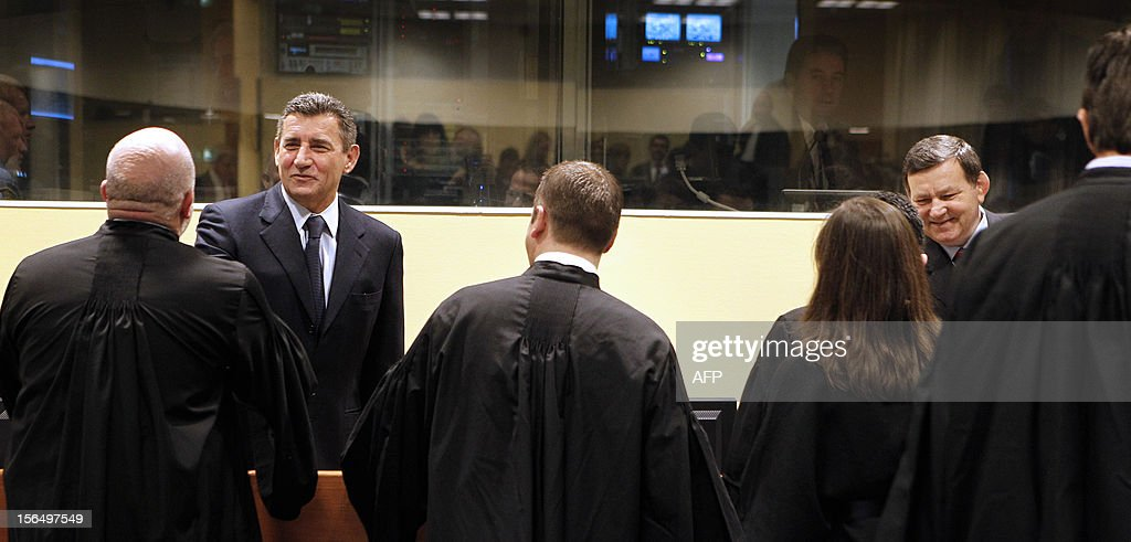 Former Croatian Army General Ante Gotovina (back, L) and Mladen Markac (back, R) shake hands with their lawyers in the courtroom of the International Criminal Tribunal for the former Yugoslavia (ICTY) prior to their appeal judgement in The Hague, The Netherlands, on November 16, 2012. The UN Yugoslav war crimes court on Friday acquitted Croatian ex-generals Ante Gotovina and Mladen Markac of charges including war crimes during the bloody breakup of Yugoslavia and ordered them freed. AFP PHOTO / ANP / POOL / Bas Czerwinski -- The Netherlands out --