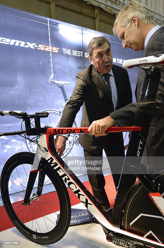 Former cyclist Eddy Merckx (L) shows his newly designed bicycle to Crown Prince Philippe of Belgium as they attend the official opening of the 91th edition of the European Motorshow in Brussels, on January 10, 2013, at the Brussels Expo. The Motorshow will open to the public from January 11 to 20.