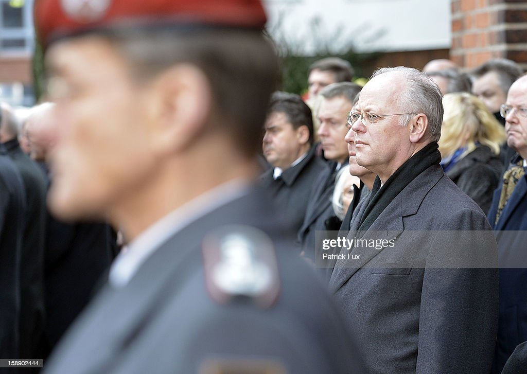 Former Defense Minister Rudolf Scharping (SPD) pays his last respect to the coffin of former German Defence Minister Peter Struck after a memorial service on January 3, 2013 in Uelzen, Germany. Struck was a leading member of the German Social Democrats (SPD) and died in December following a heart attack.