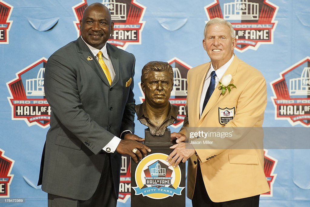 Former defensive end George Martin (L) of the New York Giants presents former head coach Bill Parcells with his Hall of Fame bust during the NFL Class of 2013 Enshrinement Ceremony at Fawcett Stadium on Aug. 3, 2013 in Canton, Ohio.