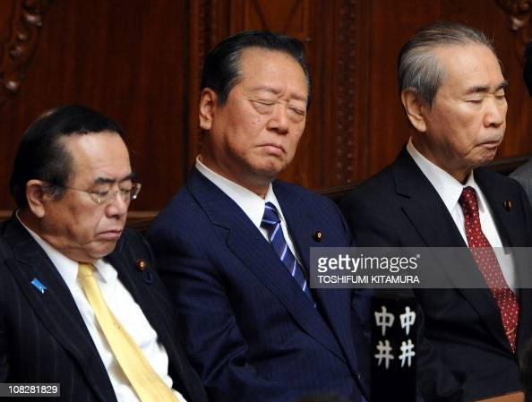 Former Democratic Party of Japan leader Ichiro Ozawa and members Hiroshi Nakai and Tsutomu Hata listen to Japanese Prime Minister Naoto Kan's policy...