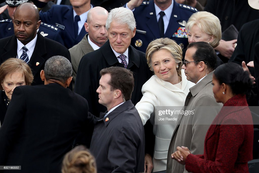 Former Democratic presidential nominee Hillary Clinton winks and shakes hands with President Barack Obama as former president Bill Clinton and Michelle Obama look on at the West Front of the U.S. Capitol on January 20, 2017 in Washington, DC. In today's inauguration ceremony Donald J. Trump becomes the 45th president of the United States.