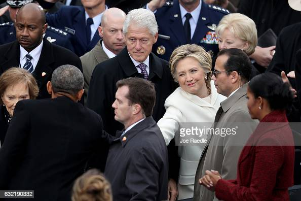 Former Democratic presidential nominee Hillary Clinton winks and shakes hands with President Barack Obama as former president Bill Clinton and...