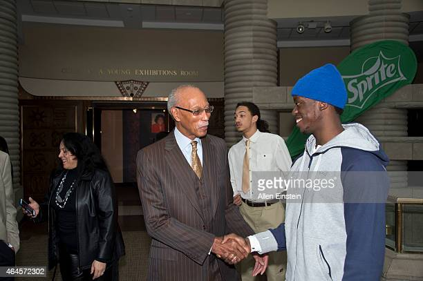 Former Detroit Mayor and NBA Legend Dave Bing and Reggie Jackson of the Detroit Pistons shake hands while touring the museum with students from...