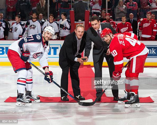 Former Detroit Red Wings players Darren McCarty and Jiri Fischer drop the ceremonial puck between captains Henrik Zetterberg of the Detroit Red Wings...