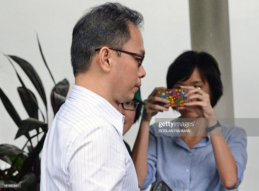 Former director of the Central Narcotics Bureau, Ng Boon Gay (L) arrives for a hearing at the Subordinate court in Singapore on February 14, 2013. Ng Boon Gay, a former head of Singapore's narcotics police was cleared of corruption on February 14 after a court rejected charges that he demanded oral sex from a contractor to help her win government deals. AFP PHOTO / ROSLAN RAHMAN