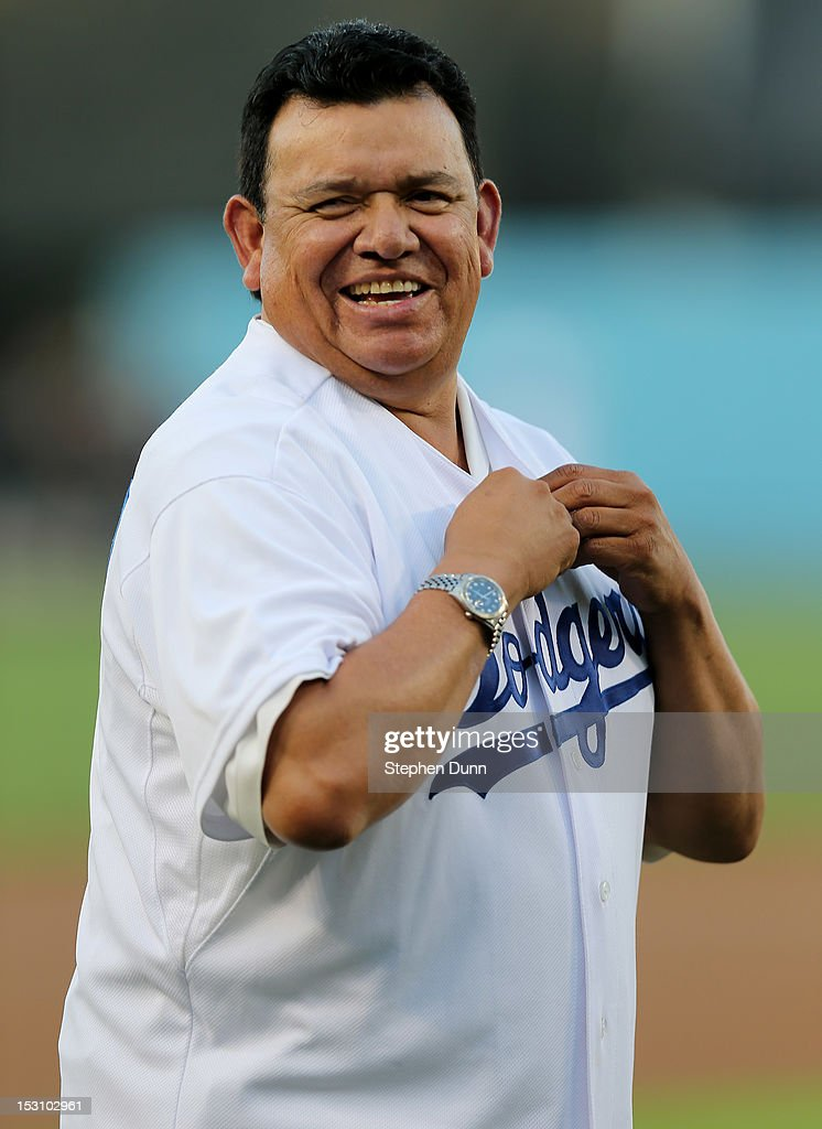 Former Dodger Hall of Fame pitcher and current Spanish language broadcaster <a gi-track='captionPersonalityLinkClicked' href=/galleries/search?phrase=Fernando+Valenzuela&family=editorial&specificpeople=217547 ng-click='$event.stopPropagation()'>Fernando Valenzuela</a> laughs as puts on a Dodger jersey for pre game ceremonies before the game between the Colorado Rockies and the Los Angeles Dodgers on September 29, 2012 at Dodger Stadium in Los Angeles, California.