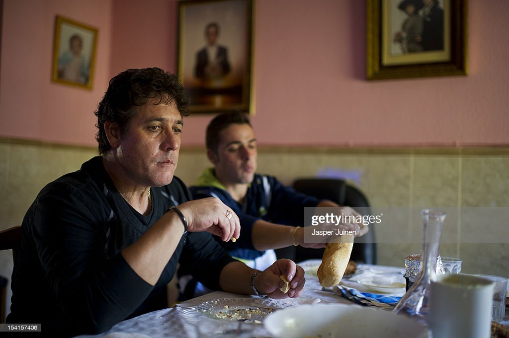 Former door factory worker, forty-eight year old unemployed father of two, Angel Perez Fernandez (L), eats lunch next to his 25 year old unemployed son, Angel, also a former door factory worker, at their home dining room on October 12, 2012 in the small industrial town of Villacanas, Spain. During the boom years, where in its peak Spain built some 800,000 houses a year, more than Britain, Germany and France combined, and millions of wooden doors where needed, the two were part of a proud elite enjoying high wages and permanent jobs. Almost all of those doors used came from this small industrial town in the La Mancha province, some seven million a year, leaving with truck loads at the same time, from the now empty and silent Villacanas industrial park. With Spain in recession and the housing bubble busted, the door industry is shattered and unemployment in Villacanas, zero for nearly a generation, is rising fast.