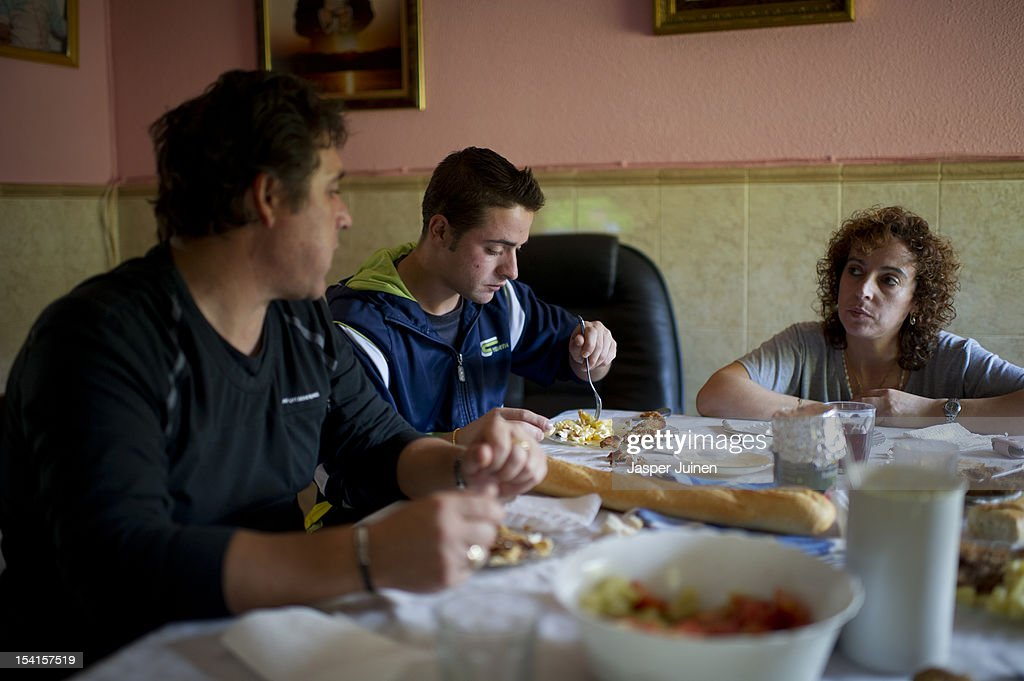 Former door factory worker, twenty-five year old unemployed Angel Perez Bueno (C), eats lunch in between his unemployed parents, former door factory worker and forty-eight year old Angel Perez Fernandez (L) and his mother, who worked as a cleaning lady at the door factories, forty year old Maria Regine Bueno Villar, at their home dining room on October 12, 2012 in the small industrial town of Villacanas, Spain. During the boom years, where in its peak Spain built some 800,000 houses a year, more than Britain, Germany and France combined, and millions of wooden doors where needed, the three were part of a proud elite enjoying high wages and permanent jobs. Almost all of those doors used came from this small industrial town in the La Mancha province, some seven million a year, leaving with truck loads at the same time, from the now empty and silent Villacanas industrial park. With Spain in recession and the housing bubble busted, the door industry is shattered and unemployment in Villacanas, zero for nearly a generation, is rising fast.