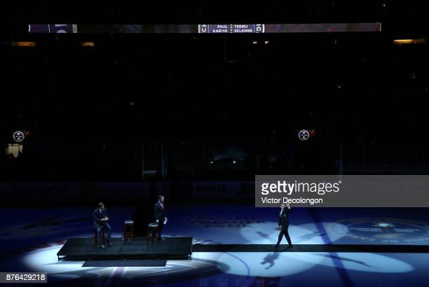 Former Ducks player Paul Kariya waves to the fans on his way to center ice to join Ducks commentator Brian Hayward and his former teammate Teemu...
