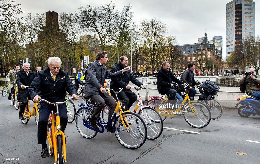 Former Dutch cyclists Joop Zoetemelk and Jan Jansen, mayor of Utrecht Aleid Wolfsen, Tour de France director Christian Prudhomme and former French cyclist Bernard Hinault ride bicycles on their way to a press conference for the official presentation of the 2015 Tour de France opening stage, on November 28, 2013 in Utrecht. Tour de France organisers Amaury Sports Organisation (ASO) revealed today that the opening stage of the Tour de France in 2015 will be an individual time-trial. ** Netherlands out **