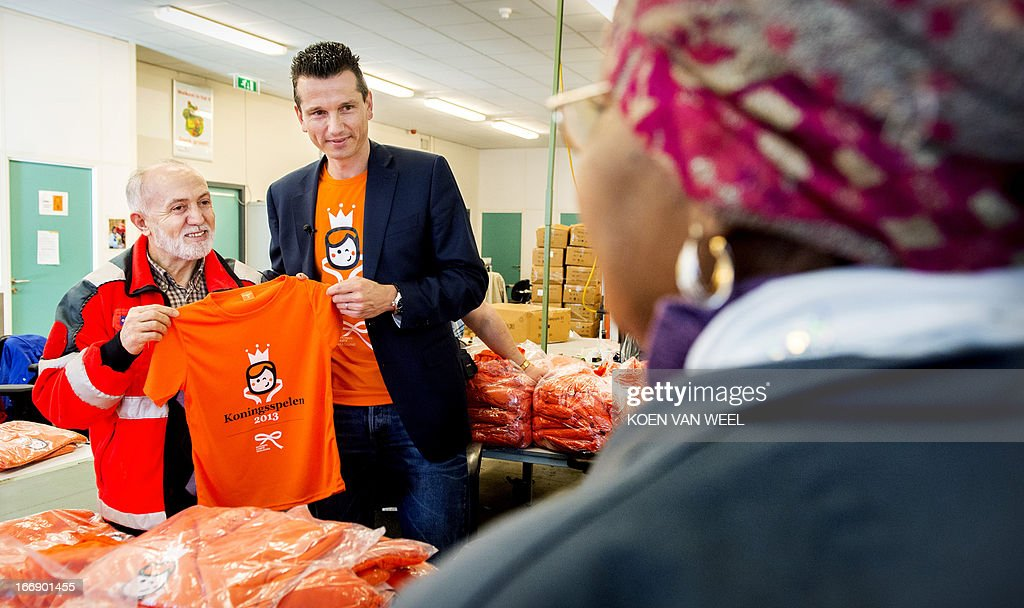 Former Dutch tennis player and member of the National Investiture Committee Richard Krajicek (R) poses with a tee-shirt for the King's Games during their presentation in Diemen, The Netherlands, on April 18, 2013. The King's Games will be a day for all children in primary schools and will be held on Friday, 26 April 2013 across the Netherlands and in the Dutch West Indies. (Man at L is unidentified). AFP PHOTO / ANP - KOEN VAN WEEL = netherlands out