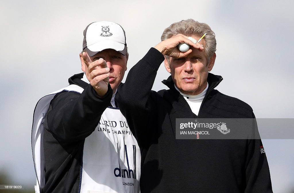 Former Eagles band member Don Felder (R) takes advice from his caddie as he takes part in the Alfred Dunhill Links Golf Championships on The Old Course at St Andrews in Scotland, on September 26, 2013.