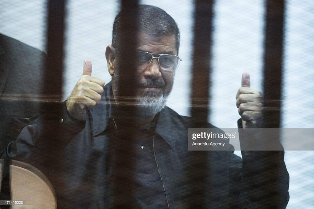Former Egyptian President Mohamed Morsi in blue clothes stands inside a glass defendant's cage during the hearing in police academy in Cairo, Egypt on April 28, 2015. Morsi attend the hearing on bule clothes because according to the Egytian Prison Regulation, defendants attend hearing in blue uniforms after sentencing. Egyptian court sentenced Morsi to 20 Years in Prison on April 21, 2015.