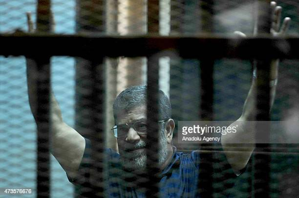 Former Egyptian President Mohamed Morsi stands inside a glass defendant's cage during the hearing in police academy in Cairo Egypt on May 16 2015 An...