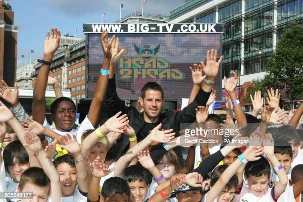 Former England and Liverpool footballer Jamie Redknapp with some of the children who formed a 'giant joystick' in front of the screen on which they...