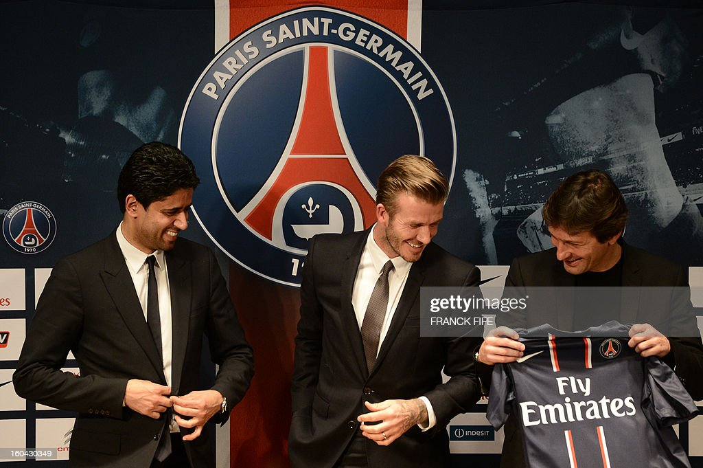 Former England captain David Beckham (C) looks at his new jersey as he gives a press conference flanked by PSG Qatari president Nasser Al-Khelaifi (L) and PSG sports director Leonardo at the Parc des Princes stadium in Paris, on January 31, 2013. Beckham on January 31 signed a five-month deal with the Ligue 1 leaders until the end of June.