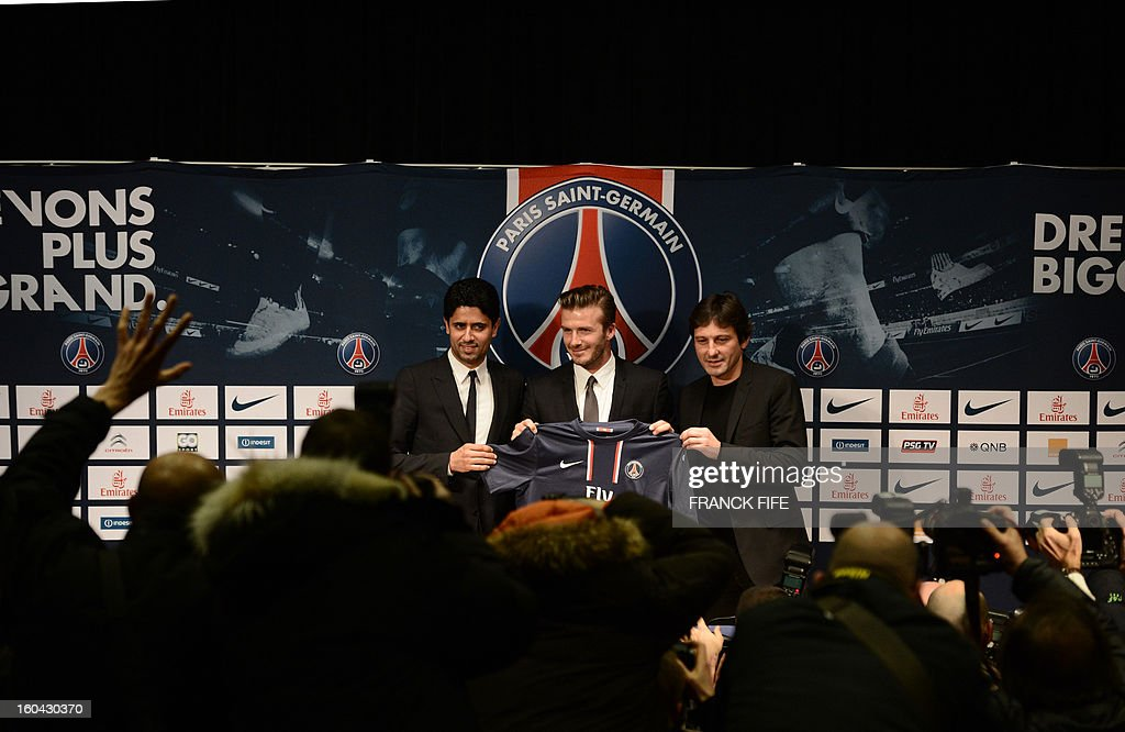 Former England captain David Beckham (C) poses with his new jersey as he gives a press conference flanked by PSG Qatari president Nasser Al-Khelaifi (L) and PSG sports director Leonardo at the Parc des Princes stadium in Paris, on January 31, 2013. Beckham on January 31 signed a five-month deal with the Ligue 1 leaders until the end of June. AFP PHOTO / FRANCK FIFE
