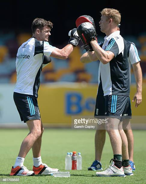 Former England cricketer Andrew Flintoff holds pads as James Anderson of England boxes ahead of a nets session at The Gabba on January 18 2015 in...
