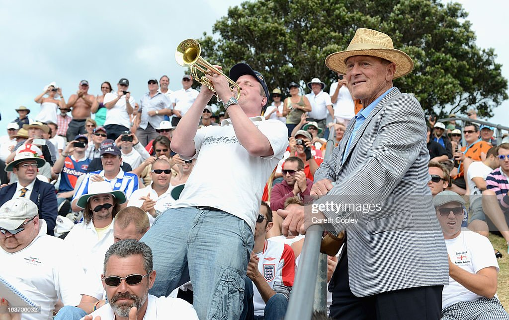 Former England cricketer Geoffrey Boycott listens to Barmy Army trumpeter Billy Cooper during day two of the second Test match between New Zealand and England at Basin Reserve on March 15, 2013 in Wellington, New Zealand.