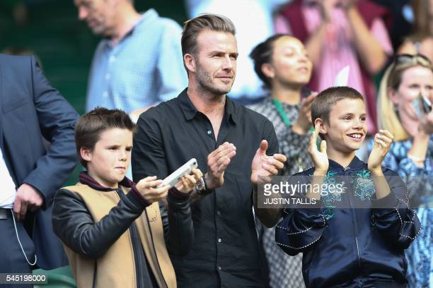 Former England footballer David Beckham and his sons Cruz and Romeo cheer Switzerland's Roger Federer's victory on centre court after he beat...