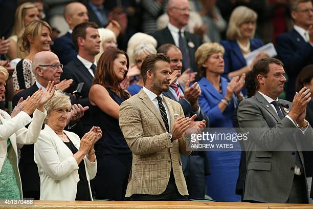 Former England footballer David Beckham stands and applauds from the royal box after Spain's Rafael Nadal won his men's singles third round match...