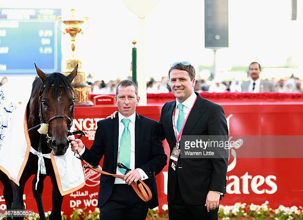 Former England international footballer Michael Owen and trainer Tom Dascombe pose with Brown Pather after winning Dubai Gold Cup during the Dubai...