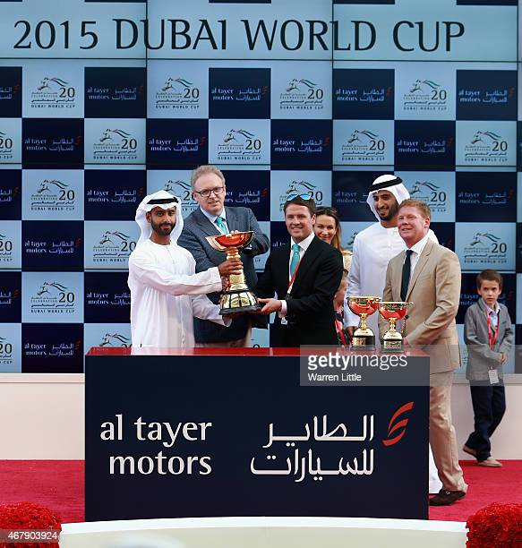 Former England international footballer Michael Owen raises the trophy after winning the Dubai Gold Cup with Brown Pather during the Dubai World Cup...