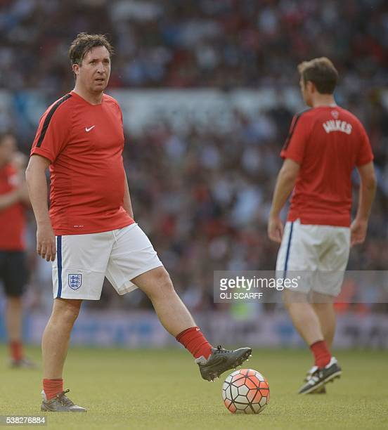 Former England international Robbie Fowler warms up before the Soccer Aid celebrity football match between England and the Rest of the World at Old...