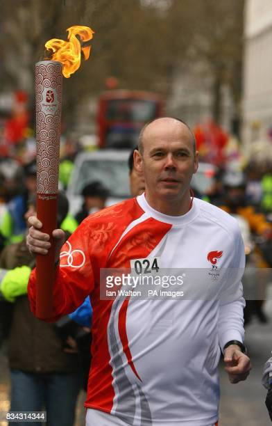 Former England rugby coach Sir Clive Woodward carries the Olympic torch during its relay journey across London on its way to the lighting of the...