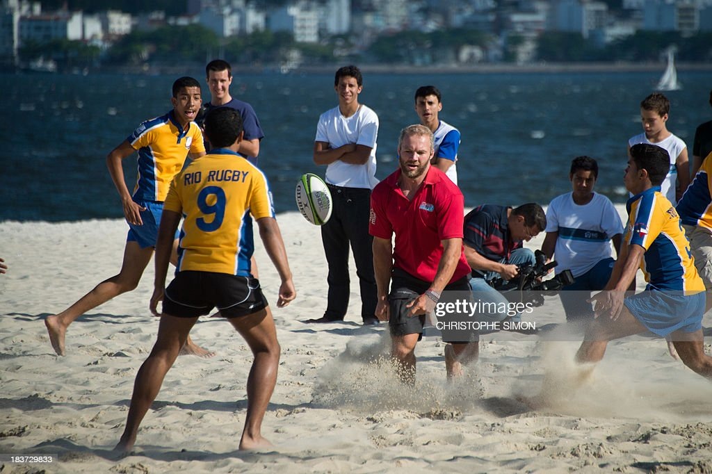 Former England Sevens' rugbier, Ollie Phillips (C), plays with residents of the Rocinha favela at Flamengo beach in an initiative supported by the Rio 2016 Organizing Commitee's Education Department on October 9, 2013 in Rio de Janeiro, Brazil.