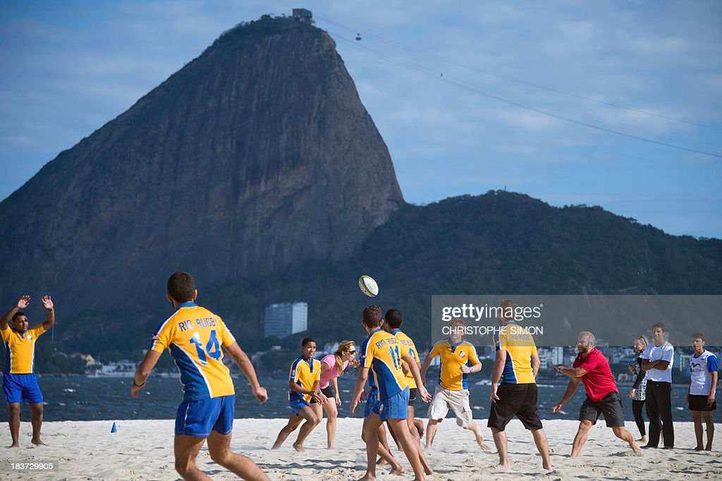 Former England Sevens' rugbier, Ollie Phillips (R), plays with residents of the Rocinha favela at Flamengo beach in an initiative supported by the Rio 2016 Organizing Commitee's Education Department on October 9, 2013 in Rio de Janeiro, Brazil. AFP PHOTO / CHRISTOPHE SIMON
