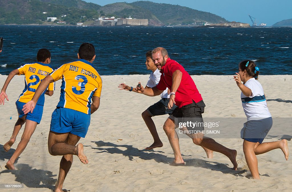Former England Sevens' rugbier, Ollie Phillips (2-R), plays with residents of the Rocinha favela at Flamengo beach in an initiative supported by the Rio 2016 Organizing Commitee's Education Department on October 9, 2013 in Rio de Janeiro, Brazil.