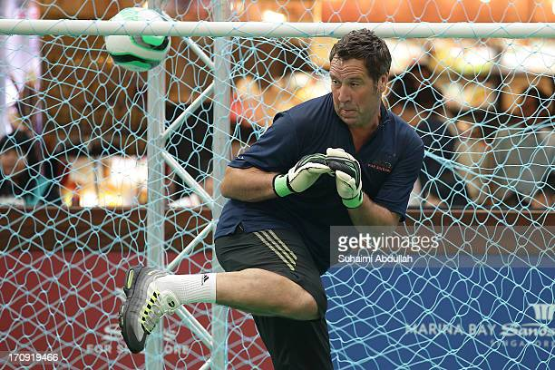 Former English football player David Seaman reacts at goal in a football clinic with students from designated charities and local Singapore schools...